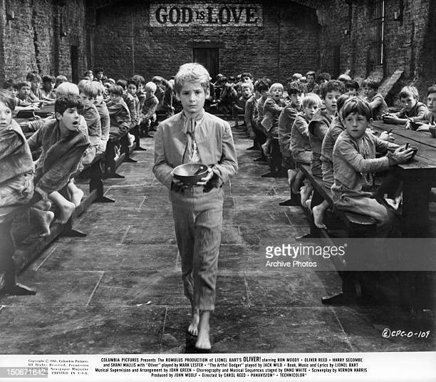 Mark Lester, playing Oliver, walking to the front of room with empty bowl in a scene from the film 'Oliver!', 1968.