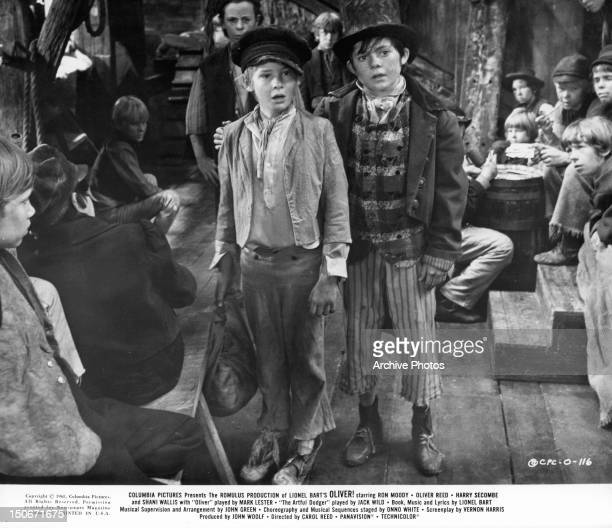 Mark Lester standing with Jack Wild, as Oliver and the Artful Dodger, in a roomful of children in a scene from the film 'Oliver!', 1968.