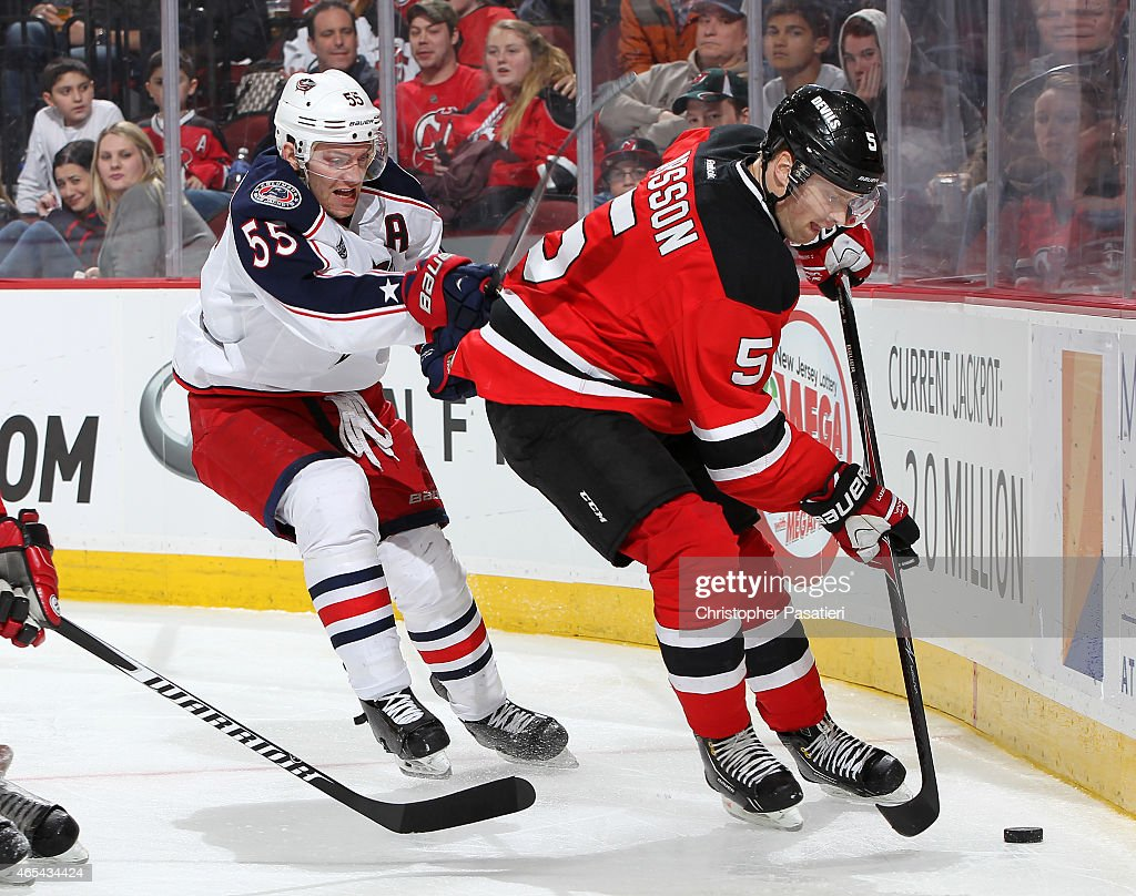 Mark Letestu #55 of the Columbus Blue Jackets checks Adam Larsson #5 of the New Jersey Devils during the third period at the Prudential Center on March 6, 2015 in Newark, New Jersey. The Blue Jackets defeated the Devils 3-2.