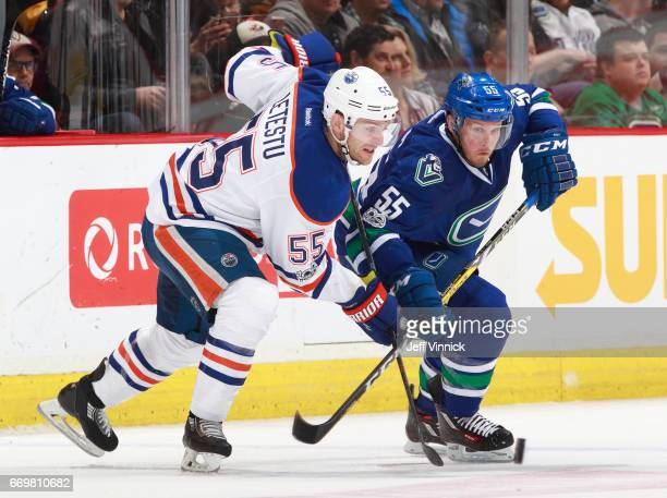 Mark Letestu of the Edmonton Oilers and Alex Biega of the Vancouver Canucks battle for a loose puck during their NHL game at Rogers Arena April 8...