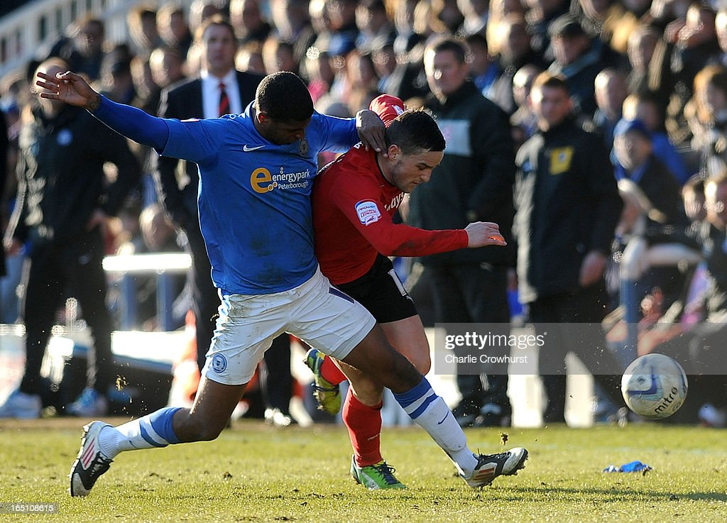 Mark Little of Peterborough puts a tackle in on Craig Conway of Cardiff City during the npower Championship match between Peterborough United and Cardiff City at London Road on March 30, 2013 in Peterborough, England,