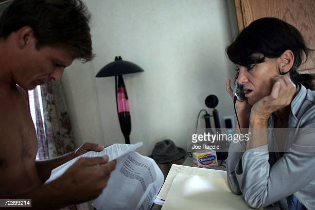 Mark M goes over paper work as his fiance Ellie Cousino talks to a Federal Emergency Management Agency agent on the phone as they call for assistance...