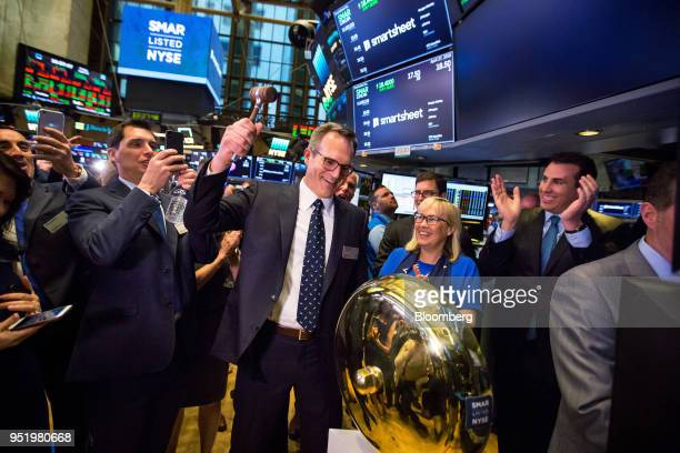 Mark Mader president and chief executive officer of Smartsheetcom Inc center rings a ceremonial bell as Jennifer Ceran chief financial officer at...