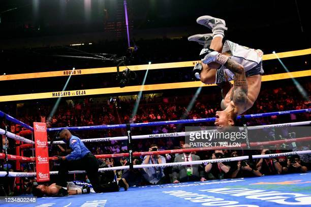 Mark Magsayo of the Philippines backflips as he celebrates after knocking down Julio Ceja of Mexico during the WBA Featherweight Title Eliminator...