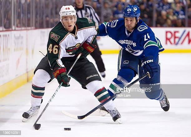 Mark Mancari of the Vancouver Canucks tries to catch Jared Spurgeon of the Minnesota Wild during the third period in NHL action on December 19 2011...