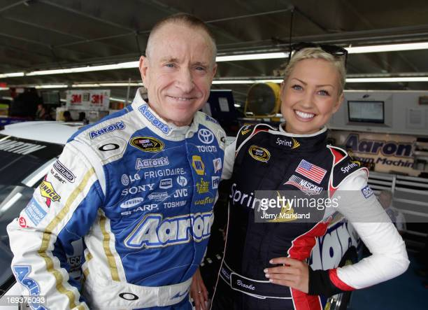 Mark Martin driver of the Aaron's Dream Machine Toyota and Miss Sprint Cup Brooke Werner stand in the garage during practice for the NASCAR Sprint...