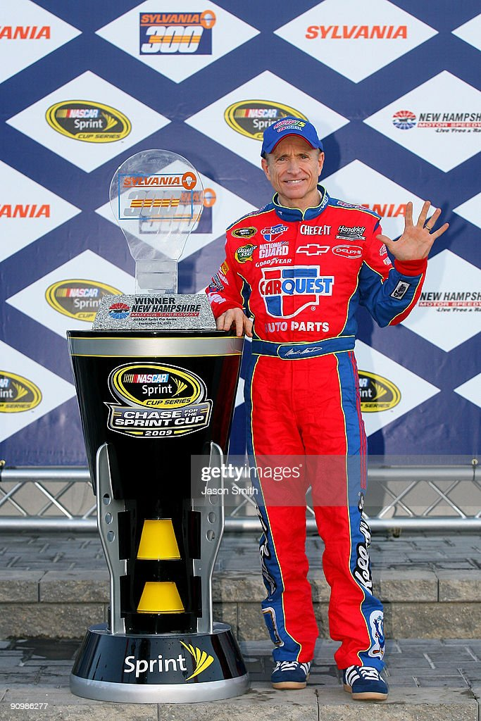 Mark Martin, driver of the #5 CARQUEST/Kellogg's Chevrolet, celebrates with the trophy in victory lane after winning the NASCAR Sprint Cup Series Sylvania 300 at the New Hampshire Motor Speedway on September 20, 2009 in Loudon, New Hampshire.