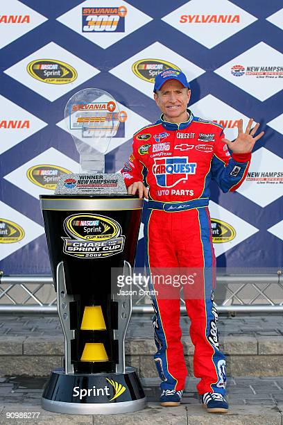 Mark Martin driver of the CARQUEST/Kellogg's Chevrolet celebrates with the trophy in victory lane after winning the NASCAR Sprint Cup Series Sylvania...