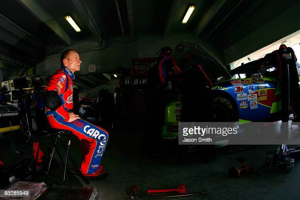 Mark Martin driver of the Kellogg's/CARQUEST Chevrolet sits in the garage as crew members work on his car in the garage during practice for the...