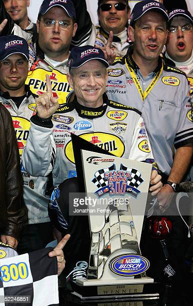 Mark Martin, driver of the Pennzoil Ford, celebrates with the trophy in victory lane during the NASCAR Busch Series Stater Bros. 300 on February 26,...