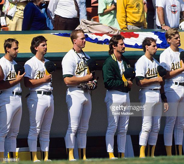 Mark McGwire and Dennis Eckersley of the Oakland A's stand among teammates during the playing of the National Anthem prior to the start of Game 1 of...