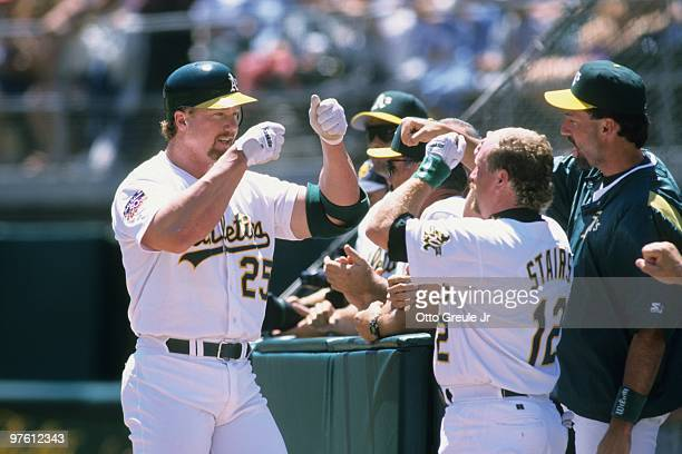 Mark McGwire of the Oakland Athletics fist bumps teammate Matt Stairs after hitting a home run during the game against the Seattle Mariners at...