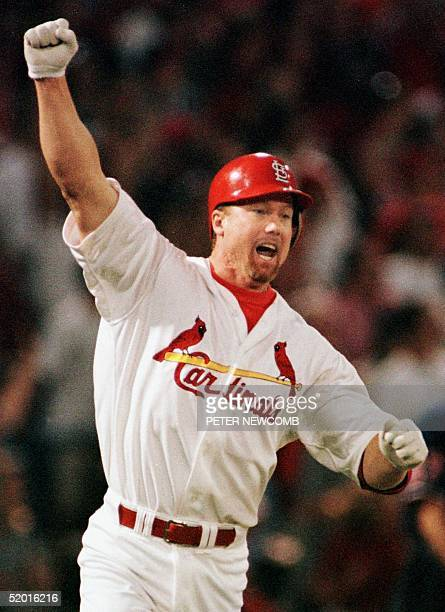 Mark McGwire of the St Louis Cardinals celebrates after hitting his 62nd homerun 08 September at Busch Stadium in St Louis MO McGwire broke the...