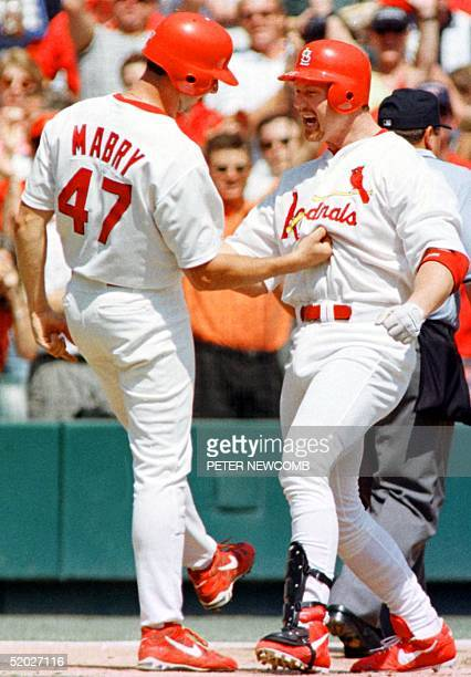 Mark McGwire of the St Louis Cardinals celebrates with teammate John Mabry after McGwire hit homerun number 60 at Busch Stadium in St Louis MO...