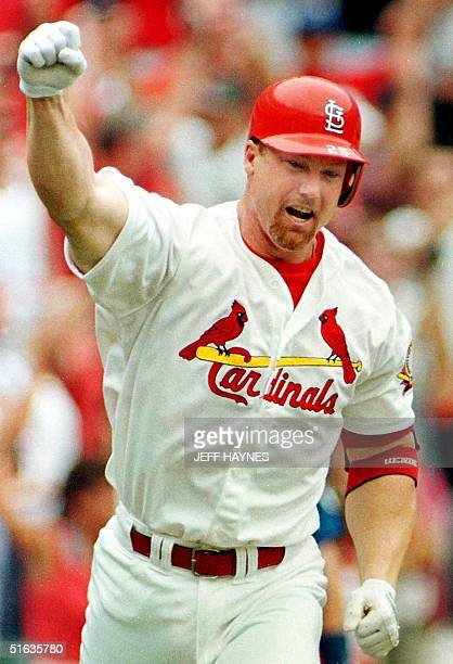 Mark McGwire of the St Louis Cardinals pumps his fist after hitting his 61st homerun 07 September at Busch Stadium in St Louis MO McGwire tied the...