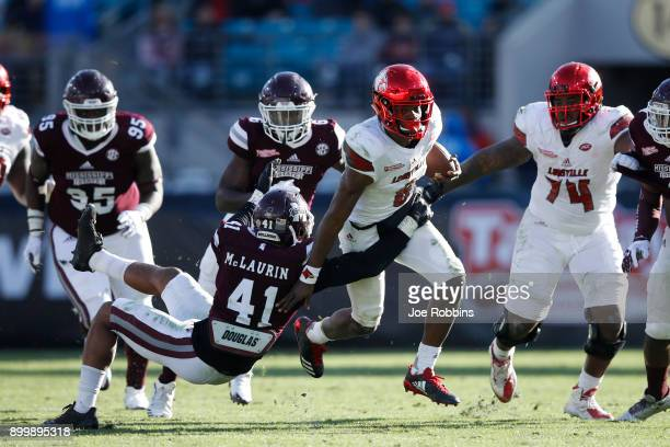 Mark McLaurin of the Mississippi State Bulldogs tackles Lamar Jackson of the Louisville Cardinals in the fourth quarter of the TaxSlayer Bowl at...