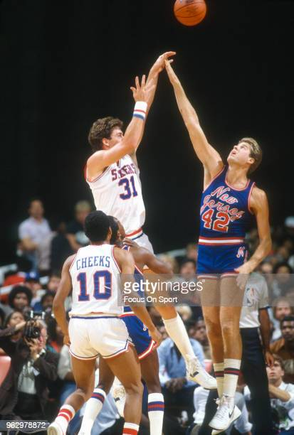 Mark McNamara of the Philadelphia 76ers shoots over Mike Gminski of the New Jersey Nets during an NBA basketball game circa 1982 at The Spectrum in...