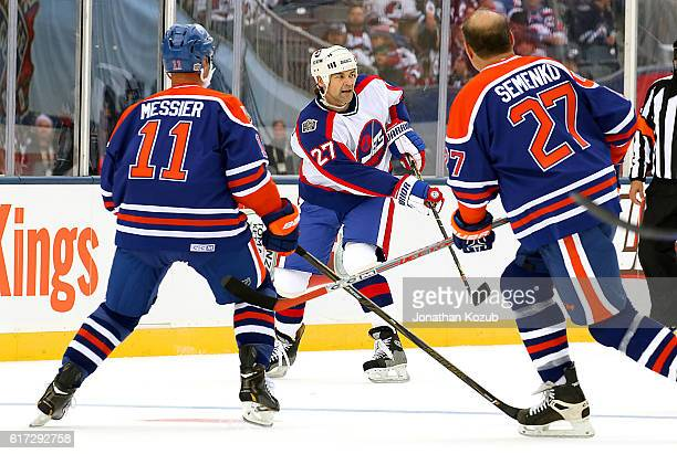 Mark Messier and Dave Semenko of the Edmonton Oilers alumni watch as Teppo Numminen of the Winnipeg Jets alumni passes the puck during first period...
