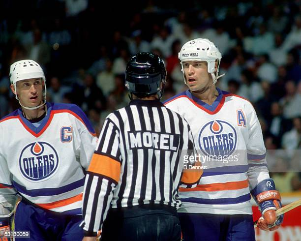 Mark Messier and Wayne Gretzky of the Edmonton Oilers question referee Denis Morel during the 1988 Stanley Cup Finals against the Boston Bruins in...