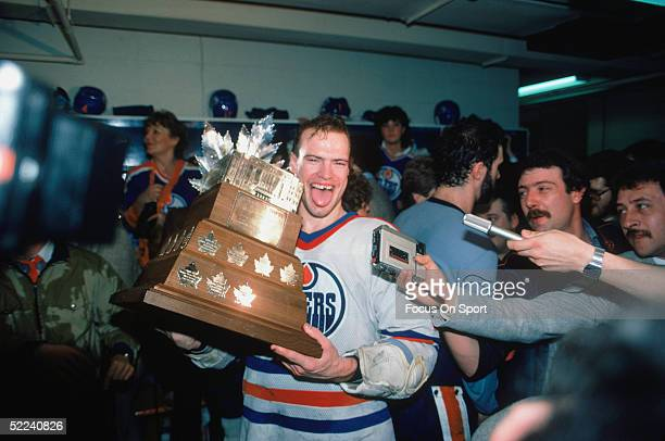 Mark Messier of the Edmonton Oilers holds the Conn Smythe Trophy in the locker room after defeating the New York Islanders for the 1984 Stanley Cup...