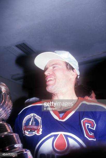 Mark Messier of the Edmonton Oilers holds the Stanley Cup Trophy in the locker room as he celebrates after Game 5 of the 1990 Stanley Cup Finals...