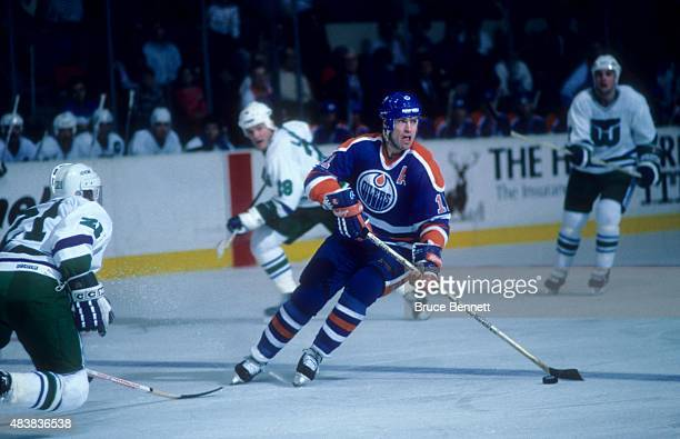 Mark Messier of the Edmonton Oilers skates with the puck during an NHL game against the Hartford Whalers circa 1987 at the Hartford Civic Center in...