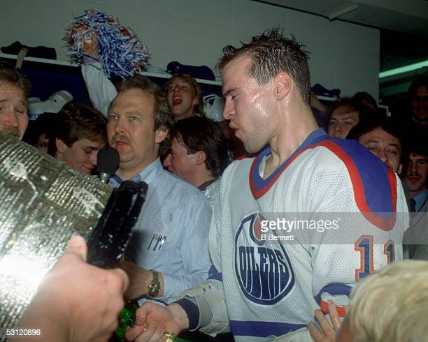 Mark Messier of the Edmonton Oilers walks towards the Stanley Cup Trophy while celebrating in the locker room after the Oilers defeated the New York...