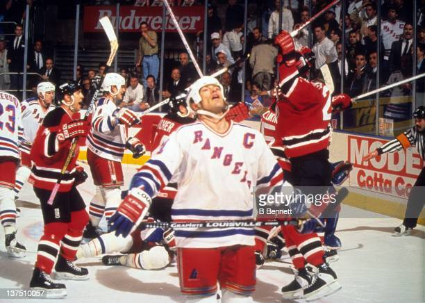 Mark Messier of the New York Rangers looks dejected as the New Jersey Devils celebrate when Valeri Zelepukin of the Devils scored the tying goal with...