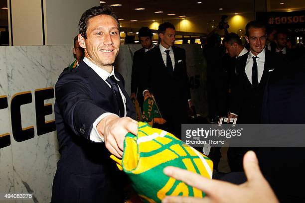 Mark Milligan of Australia hands a fan his Socceroos scarf prior to departing for Brazil ahead of the 2014 FIFA World Cup at Sydney International...