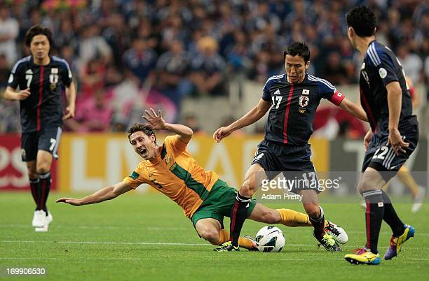 Mark Milligan of Australia is tackled by Makoto Hasebe of Japan during the FIFA World Cup qualifier match between Japan and Australia at Saitama...