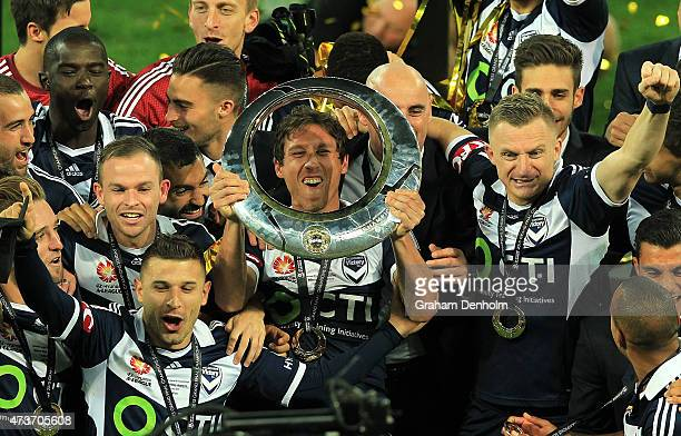 Mark Milligan of Melbourne Victory holds the trophy as he celebrates with his teamates following victory in the 2015 ALeague Grand Final match...