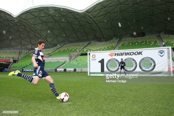 Mark Milligan of the Victory aims for the 1000th match banner with Victory goal keeper Nathan Coe standing guard during an ALeague 1000th match media...