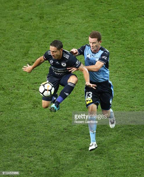 Mark Milligan of the Victory is challenged by Brandon O'Neill of Sydney FC during the round 18 ALeague match between Melbourne Victory and Sydney FC...