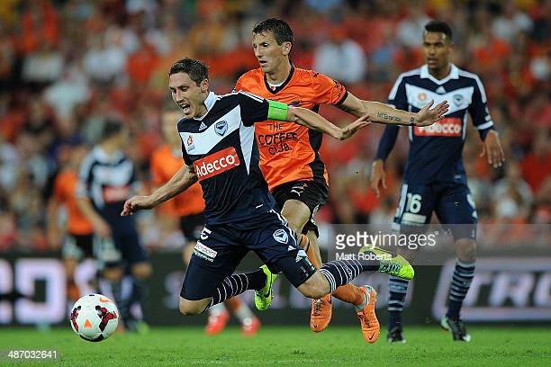 Mark Milligan of the Victory is tackled by Liam Miller of the Roar during the ALeague Semi Final match between the Brisbane Roar and Melbourne...