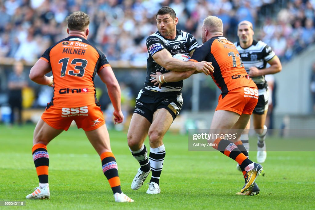 Mark Minichiello of Hull FC is challenged by Oliver Holmes and Adam Milner of Castleford Tigers during the Betfred Super League match between Hull FC and Castleford Tigers at KCOM Stadium on May 5, 2018 in Hull, England.