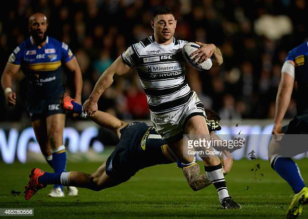Mark Minichiello of Hull FC jumps from a tackle from Adam Cuthbertson of Leeds Rhinos during the First Utility Super League match between Hull FC and...