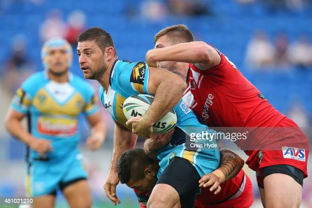 Mark Minichiello of the Titans is tackled during the round 15 NRL match between the Gold Coast Titans and the St George Illawarra Dragons at Cbus...