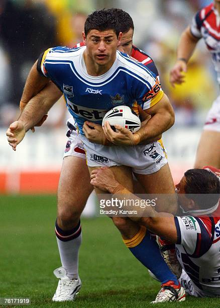 Mark Minichiello of the Titans is tackled during the round 23 NRL match between the Gold Coast Titans and the Sydney Roosters at Carrara Stadium on...