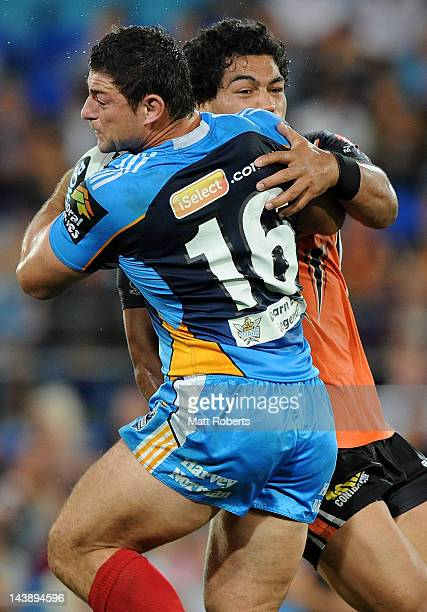Mark Minichiello of the Titans is tackled during the round nine NRL match between the Gold Coast Titans and the Wests Tigers at Skilled Park on May...