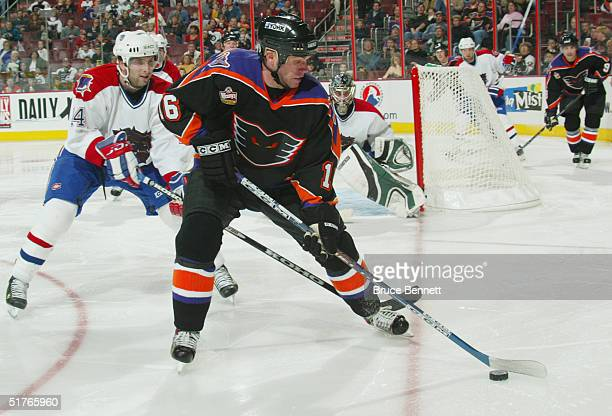 Mark Murphy of the Philadelphia Phantoms keeps the puck from MarcAndre Thinel of the Hamilton Bulldogs during the American Hockey League game on...