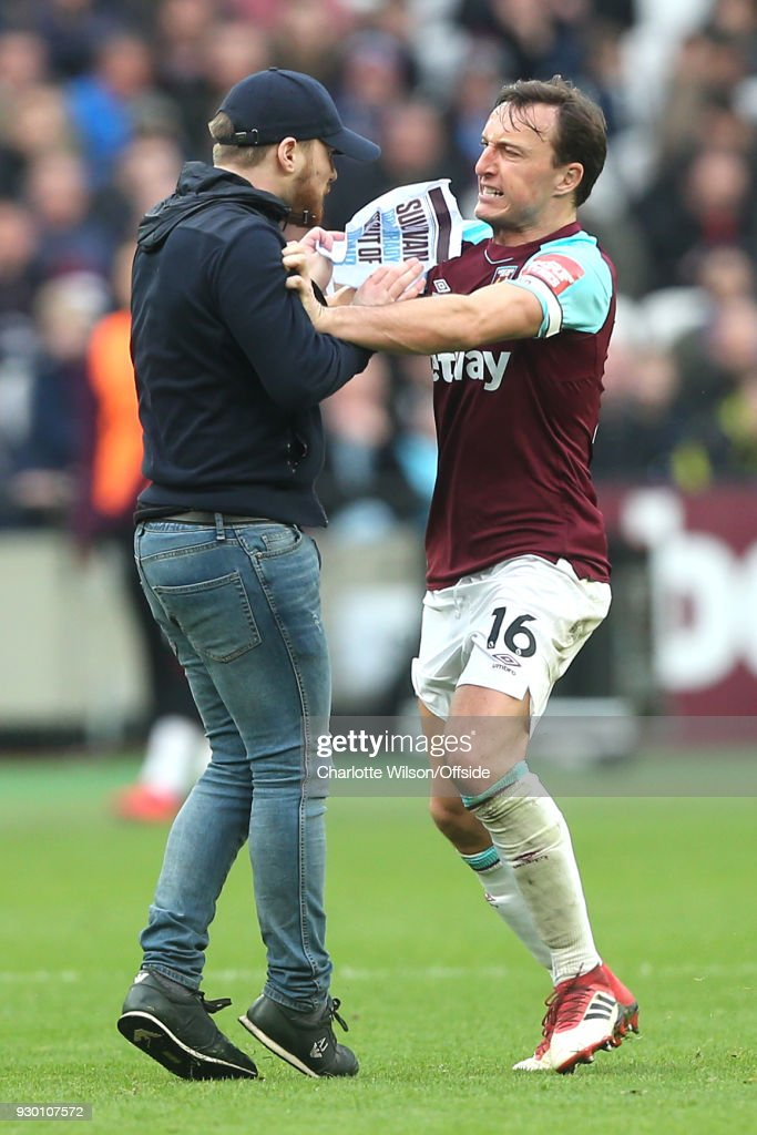 Mark Noble of West Ham fights with a pitch invader protesting the board of directors during the Premier League match between West Ham United and Burnley at London Stadium on March 10, 2018 in London, England.