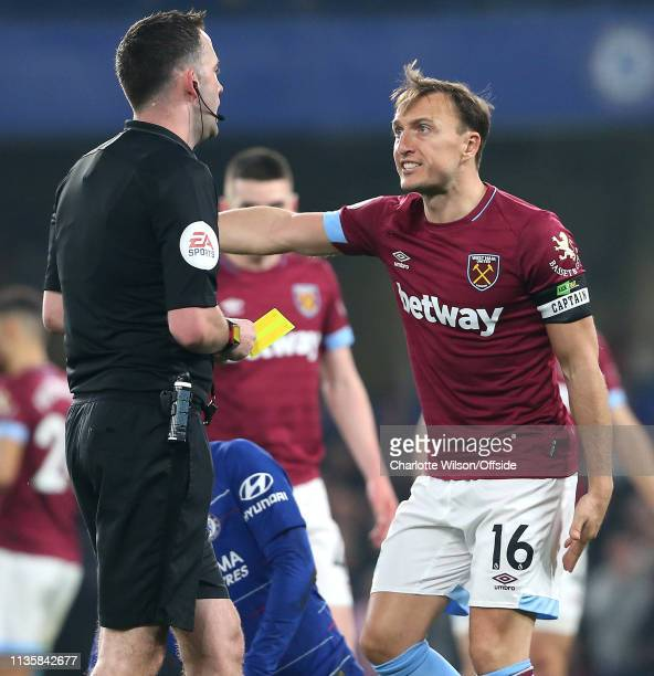 Mark Noble of West Ham speaks angrily with referee Christopher Kavanagh over a yellow card decision during the Premier League match between Chelsea...