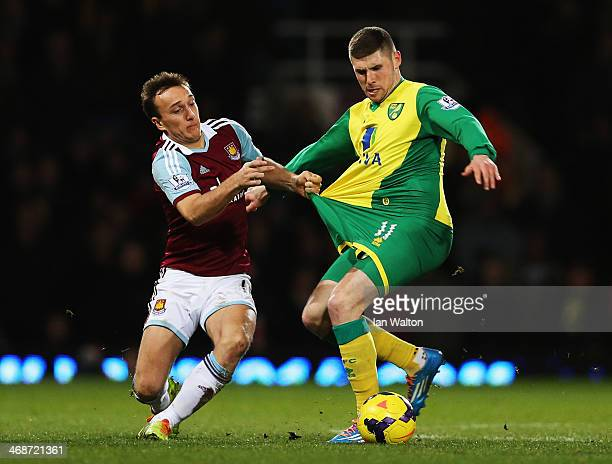 Mark Noble of West Ham United and Gary Hooper of Norwich City challenge for the ball during the Barclays Premier League match between West Ham United...