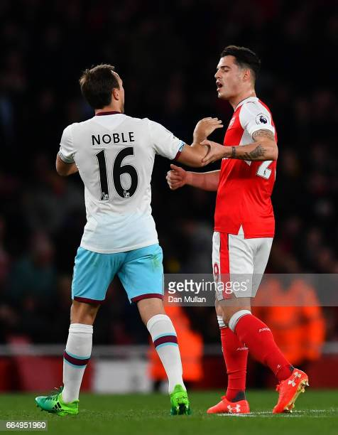 Mark Noble of West Ham United and Granit Xhaka of Arsenal exchange words during the Premier League match between Arsenal and West Ham United at the...