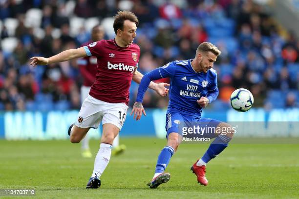 Mark Noble of West Ham United battles for possession with Joe Bennett of Cardiff City during the Premier League match between Cardiff City and West...