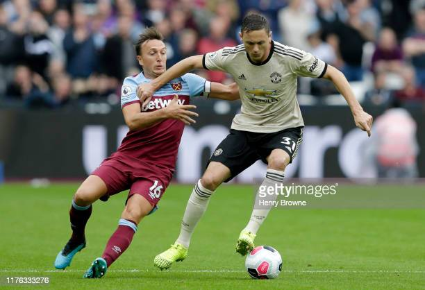 Mark Noble of West Ham United battles for possession with Nemanja Matic of Manchester United during the Premier League match between West Ham United...