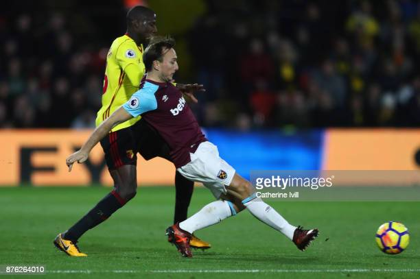 Mark Noble of West Ham United beats Abdoulaye Doucoure of Watford to the ball during the Premier League match between Watford and West Ham United at...