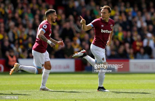 Mark Noble of West Ham United celebrates with Manuel Lanzini after scoring their first goal during the Premier League match between Watford FC and...