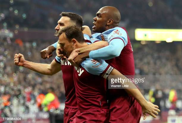 Mark Noble of West Ham United celebrates with Robert Snodgrass and Angelo Ogbonna after scoring his team's first goal with his team mates during the...