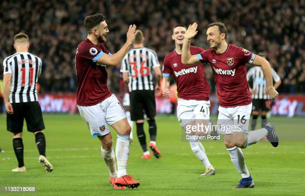 Mark Noble of West Ham United celebrates with teammates after scoring his team's second goal during the Premier League match between West Ham United...